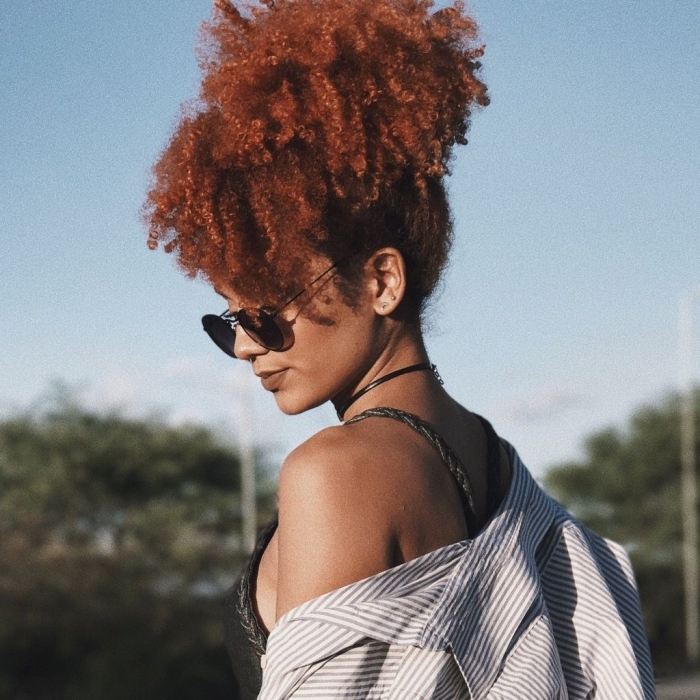 comment styliser les cheveux ondulés ou frisés, modèle de coiffure de style afro puff avec mèches tombantes sur le devant