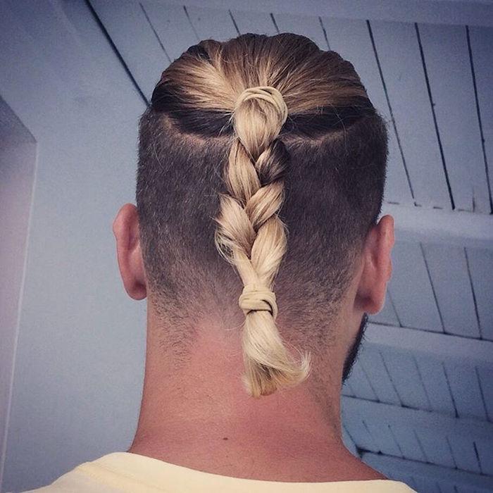 homme brun avec coloration balayage blond sur le dessus avec cheveux mi long avec tresse sur queue de cheval