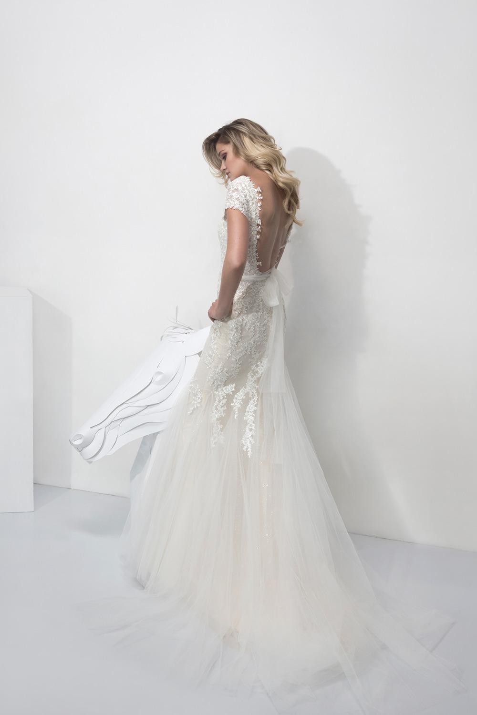 silhouette féminine et élégante en robe de mariée fourreau en dentelle et tulle avec un décolleté dos sensuel mis en valeur par un noeud en tulle