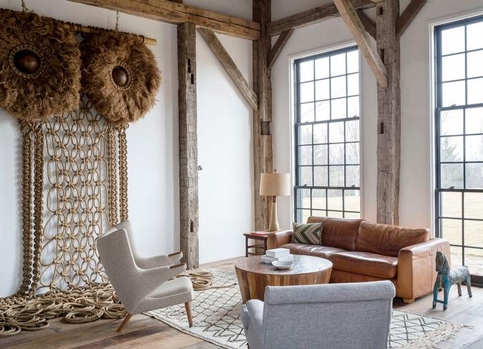 salon à design rustique avec meubles de bois et cuir aux murs blancs avec colonnes en bois brut, modèle suspension murale macramé