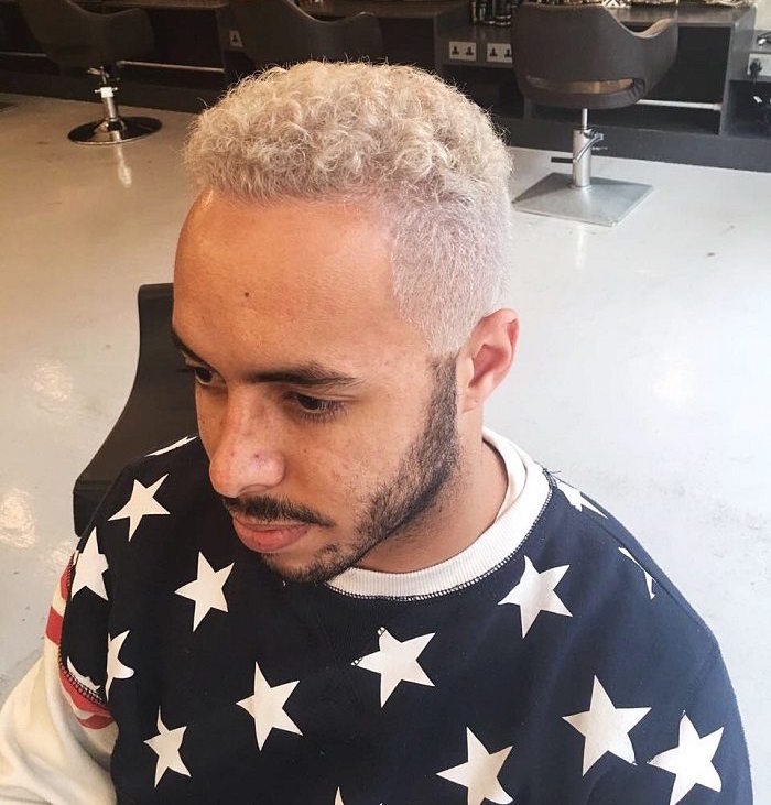 mèche platine et teinture blonde homme aux cheveux bouclés en dégradé