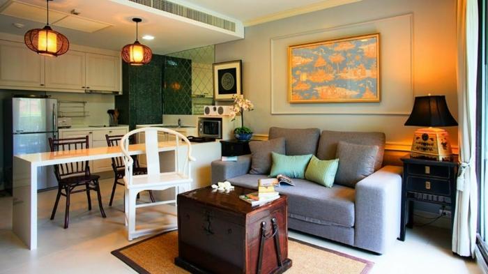 valise vintage en bois, tapis jaune, table blanche, chaises en bois foncé, sofa gris, chaise peinte blanche, petite cuisine ouverte