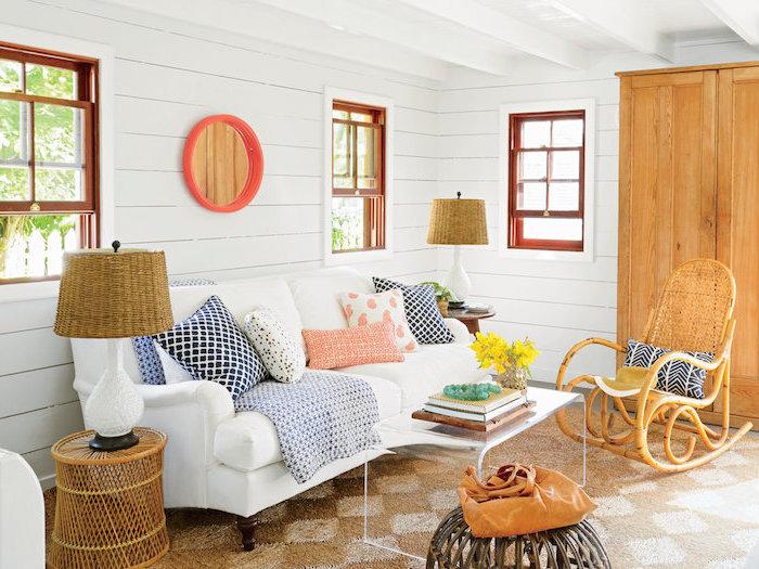 deco salon cosy, lambris mural blanc, canapé blanc décoré de coussins colorés, petite table metallique, tapis marron, chaise à bascule rotin