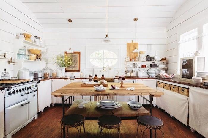 cuisine campagne chic en lambris blanc mural, parquet bois marron foncé, établi bois et tabourets de bar, meuble bas cuisine blanc, étagères bois ouvertes
