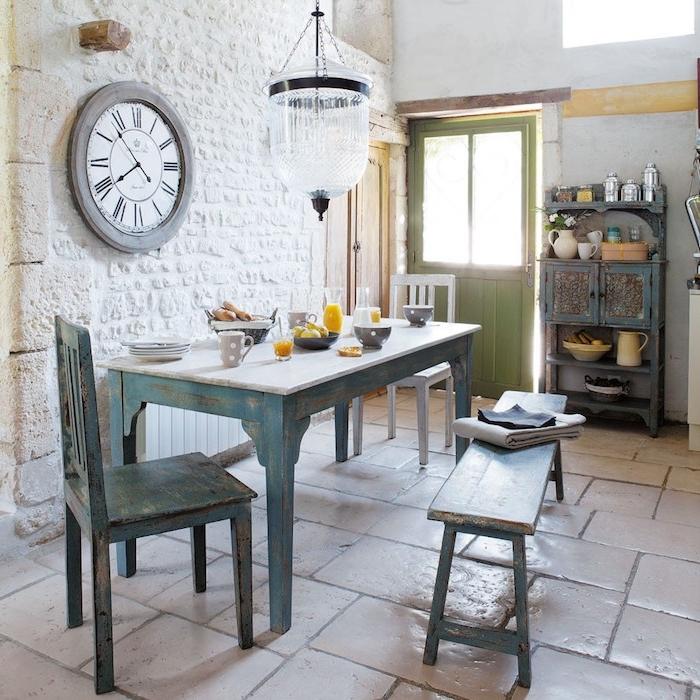 mur de briques blanches, table, chaise et bancs en bois brut couleur bleue, carrelage sol retro, vaisselier vintage, deco anglaise de campagne