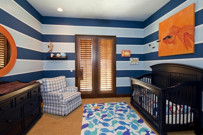 tapis blanc aux motifs poissons, fauteuils carreaux, miroir rond, peinture murale rayures bleues, chambre garcon bebe