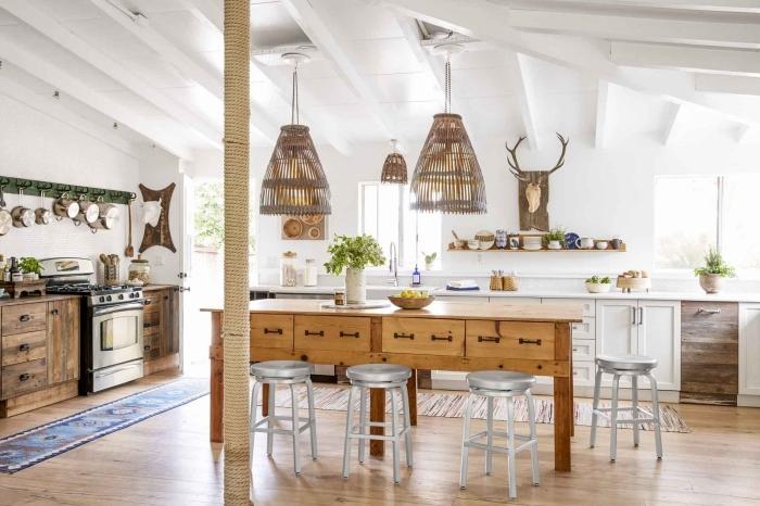 une table ancienne en bois avec des tiroirs intégrés qui fait office d'un ilot central cuisine, une cuisine spacieuse rustique chic pleine de charme