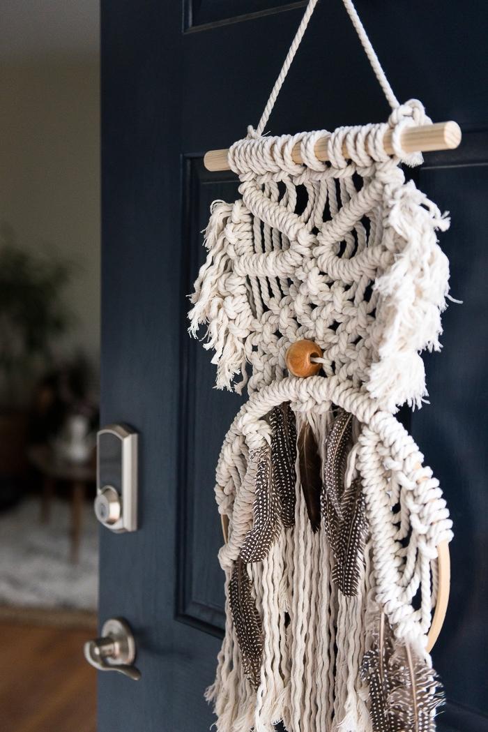objet DIY réalisé avec la technique noeuds macramé et décoré avec plumes et perles de bois, déco de porte avec création macramé