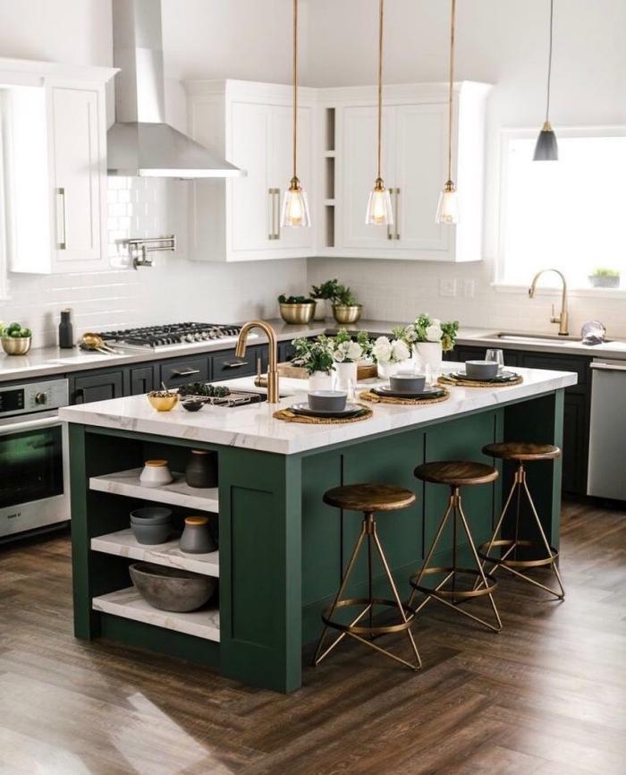 un ilot de cuisine avec espace bar plein de caractère grâce à l'association d'un plan de travail en marbre et le vert saturé de la structure de base