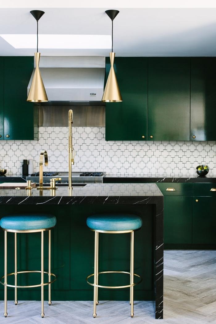 cuisine design modern en vert sapin et noir aux accents dorés équipée d'un ilot centrale avec comptoir de marbre noir à veines subtils