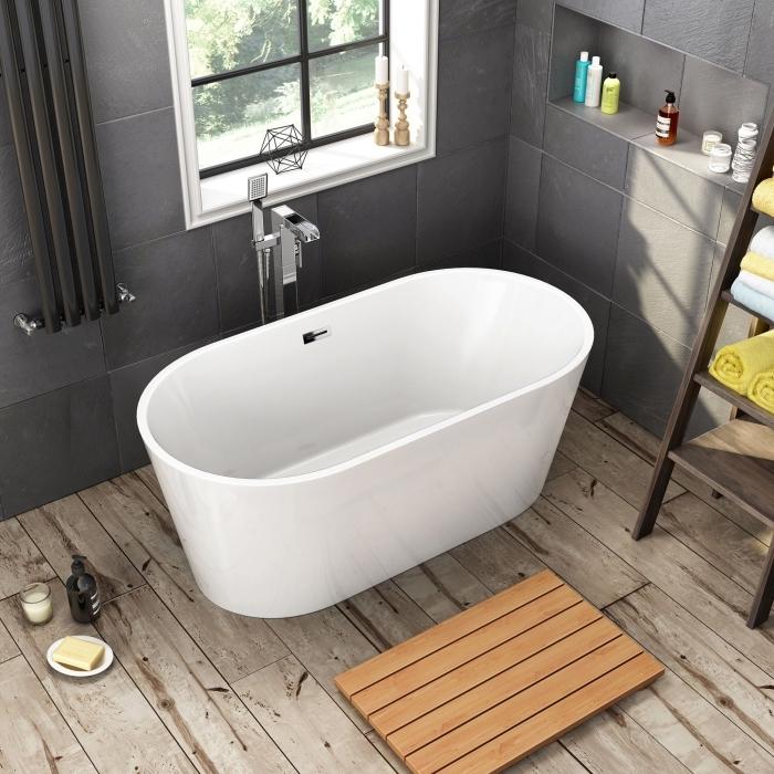 rangement gain place dans une petite salle de bain aux murs gris avec niches murales, modèle de petite baignoire sabot