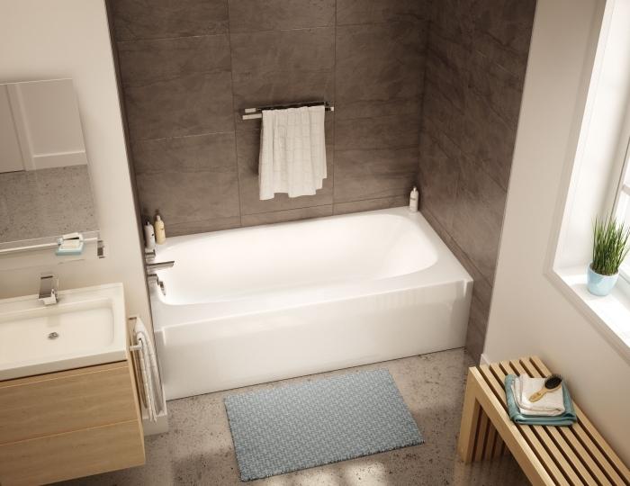 modèle de petite baignoire intégrée dans une salle de bain en couleurs neutres et meubles de bois clair avec large miroir