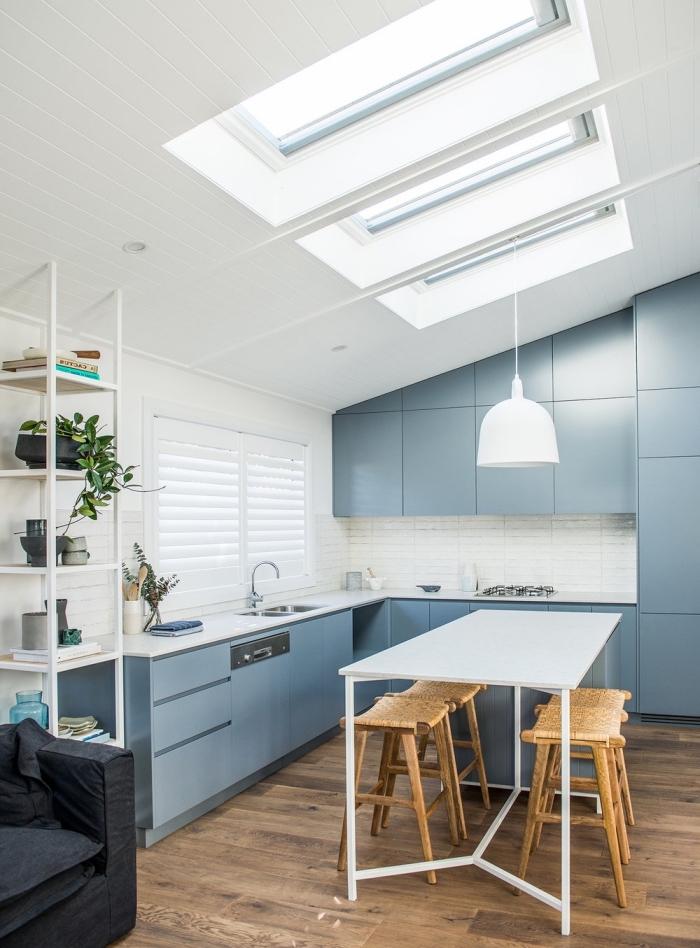 aménagement d'une cuisine avec des armoires laquées bleu-gris mat meublé d'un ilot central table blanche qui introduit une touche conviviale