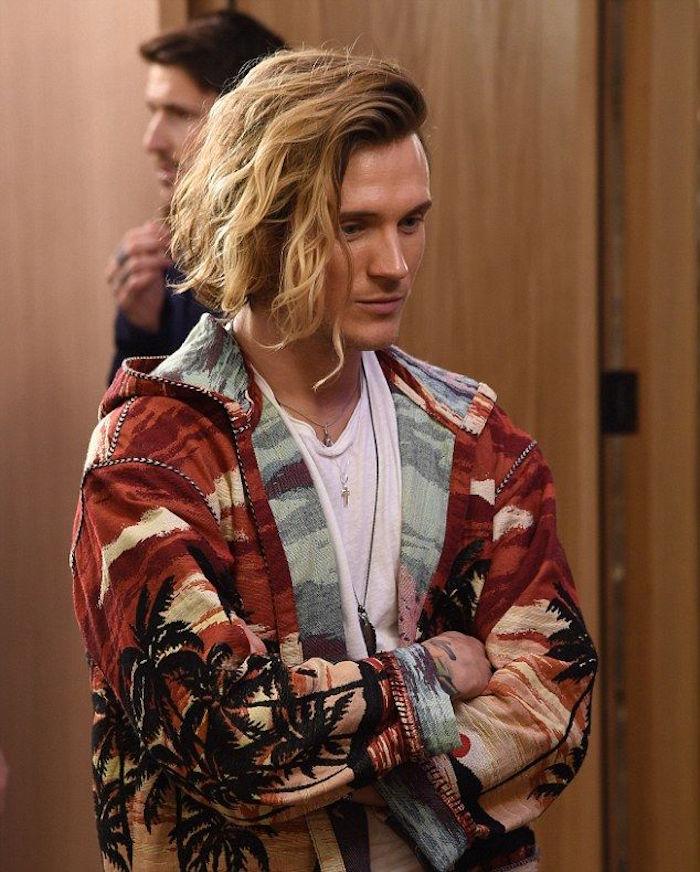 coupe de cheveux mi long ondulé avec mèche blonde pour homme en balayage et veste rétro tropical
