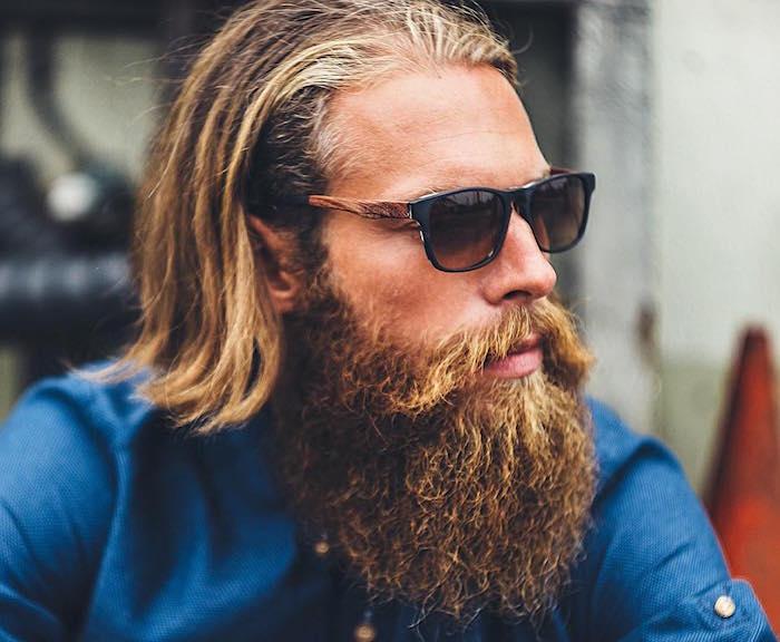 hipster homme avec barbe longue et coiffure mi longue avec meche blonde sur cheveux chatain