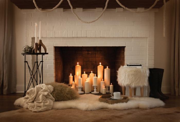 plusieurs bougies allumées, manteau de cheminée en briques blanches, fourrure blanche
