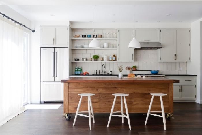 cuisine avec ilot central à roulettes recouvert entièrement en bois, contrastant avec le blanc des carreaux de métro et des armoires