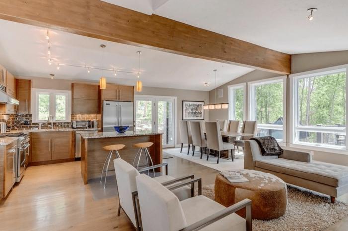 joli intérieur en bois et blanc, grandes chaises confortables, tabouret rond, poutres au plafond blanc, separation cuisine salon