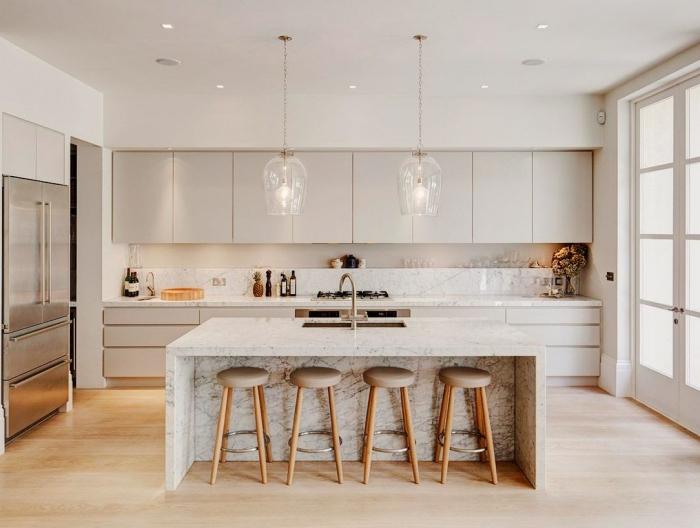cuisine avec ilot en marbre uni avec zone de lavage au centre et un coin bar de l'autre côté, mis en valeur par les deux luminaires suspendus en verre
