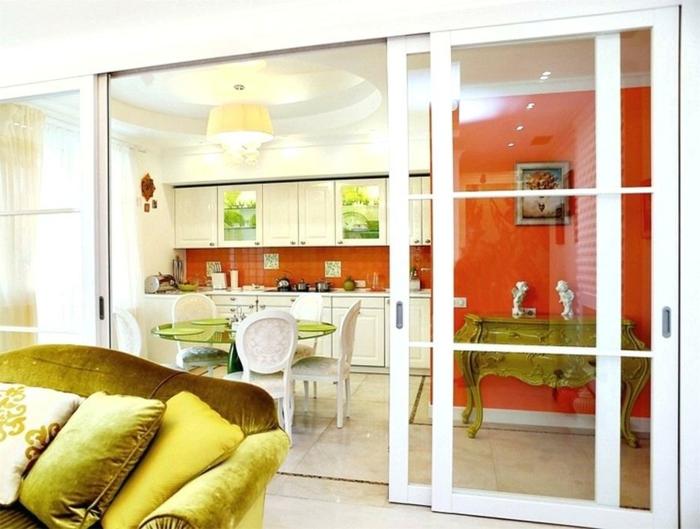 aménagement cuisine avec verriere, console baroque, table ronde verte, chaises médaillon blanches, mur et crédence rouges