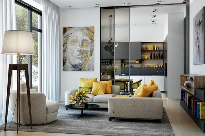 lampe de sol blanche, tapis gris, sofa d'angle gris, portrait style grecque, cloison vitrée du sol au plafond, cuisine avec verriere