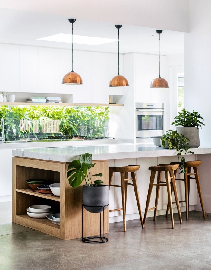 une cuisine blanche et bois avec îlot central de cuisine en bois naturel et quartz blanc, disposant d'un espace de rangement supplémentaire à son extrémité et d'un coin bar convivial