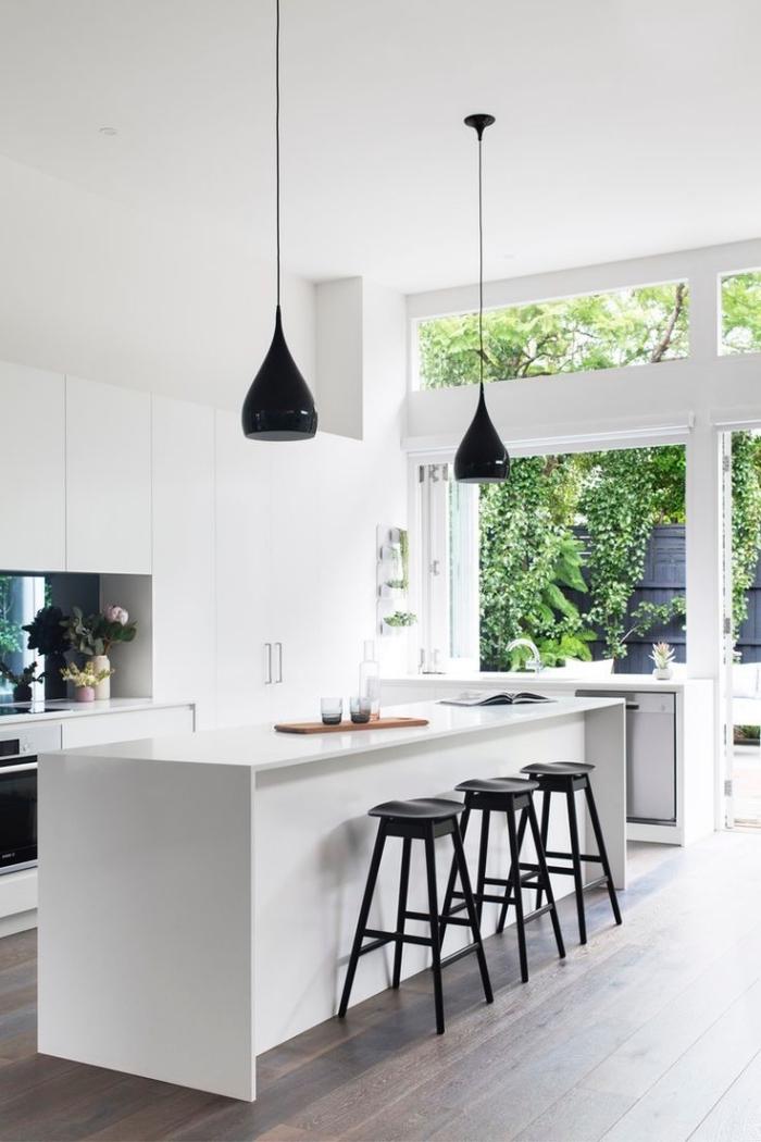 une cuisine à plan ouvert baignée de lumière naturelle équipée d'un ilot central cuisine minimaliste avec espace bar aux touches noires