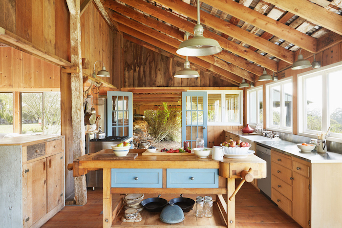 cuisie exterieur style campagne chic, poutres apparentes, meuble cuisine bois et établi bois à tiroirs repeints en bleu, suspensions campagne
