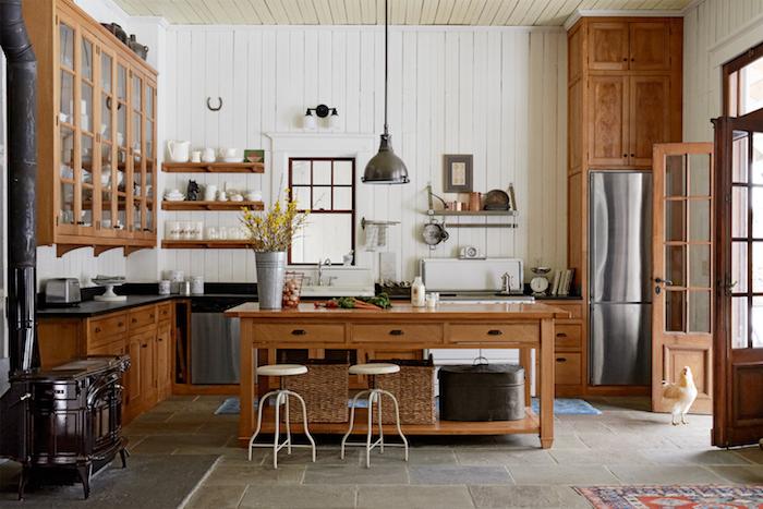 amenagement cuisine campagne chic avec établi bois, tabourets de bar, meuble bas bois et vaisselier bois haut, carrelage carreaux de pierre, lambris blanc, suspension style cottage