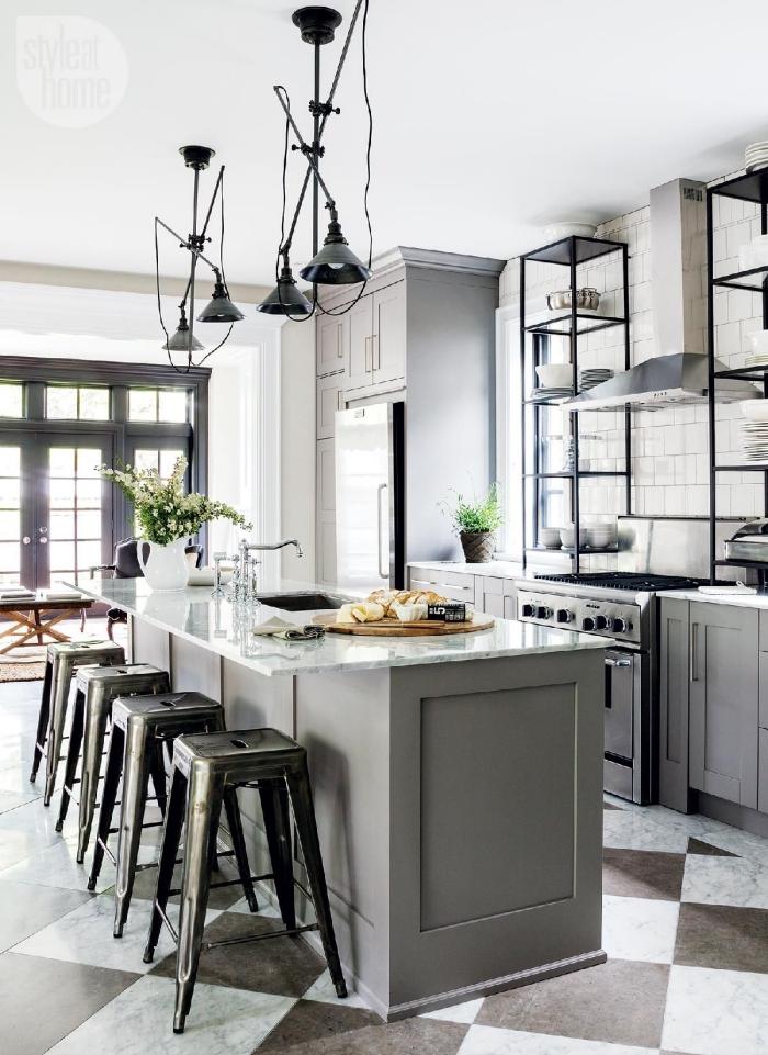 une cuisine gris clair qui mélange les style traditionnel et industriel, à la fois fonctionnelle et conviviale grâce à l'ilot de cuisine plan bar à comptoir en quartz