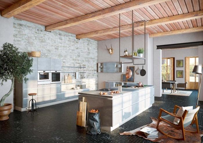 ilot central cuisine en béton d'aspect brut, surmonté d'une étagère en métal suspendue au mur, aménagé dans une cuisine d'esprit atelier industriel