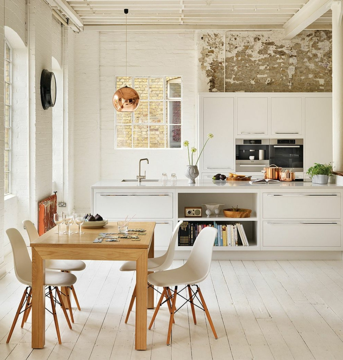salle à manger et cuisine scandinave, table en bois, chaises scandinaves, lampe cuivrée, ilot de bar blanc, mur blanc au cachet indus