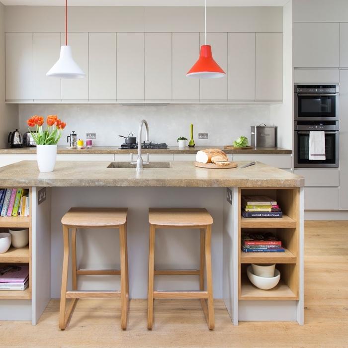 une cuisine gris clair d'esprit scandinave avec plan de travail ilot central en granit contrastant avec la structure de base