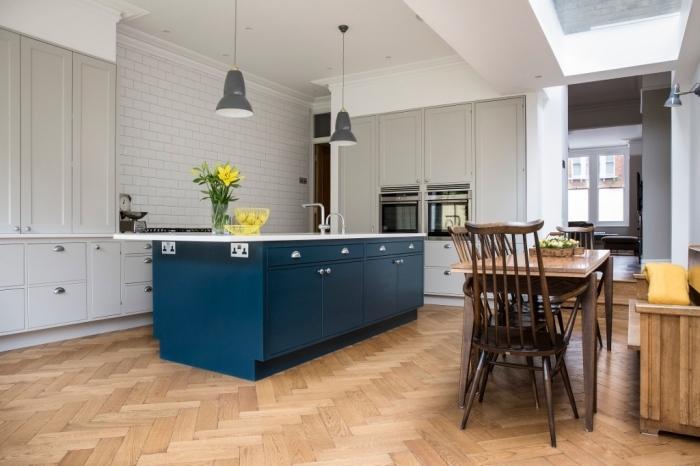 cuisine gris clair et blanc avec ilot de cuisine contrastant en bleu marine, mélange de style rustique et industriel dans cette cuisine ouverte sur la salle à manger