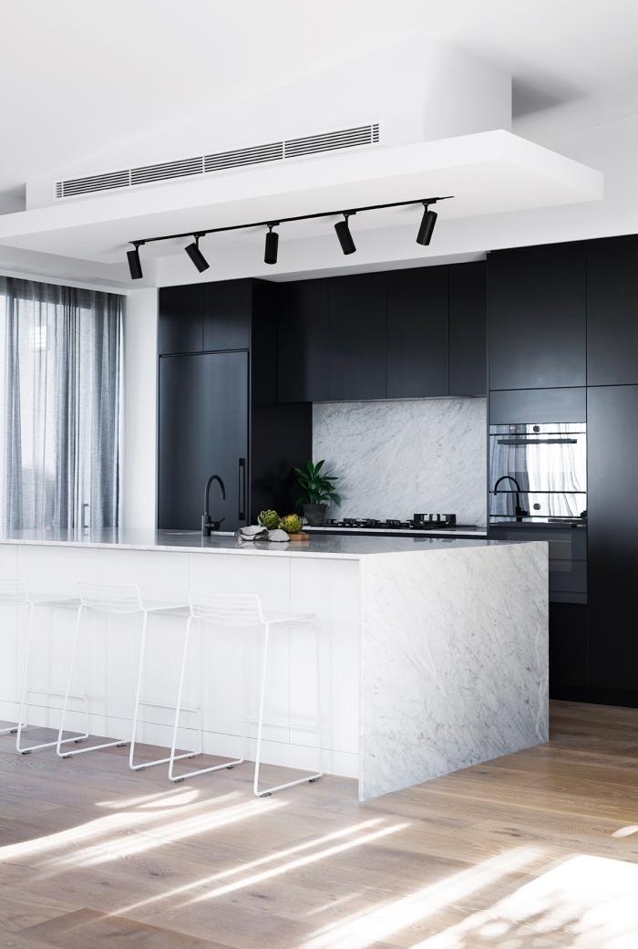 contraste saisissant entre les armoires de cuisine à finition noire mate et le plan de travail ilot central en marbre veiné accessoirisé avec des tabourets de bar en fil de métal blanc