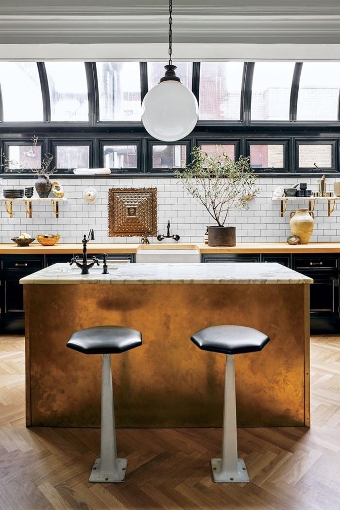 cuisine ilot central qui se fait un élément accrocheur dans cet espace vintage scandinave avec son comptoir en marbre et sa façade effet cuivre qui s'harmonise avec les supports des étagères ouvertes
