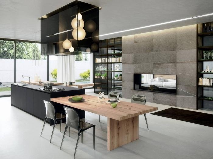 cuisine ouverte aux lignes épurées et contemporaines équipée d'un ilot centrale avec table en bois naturel et évier laqué noir mat