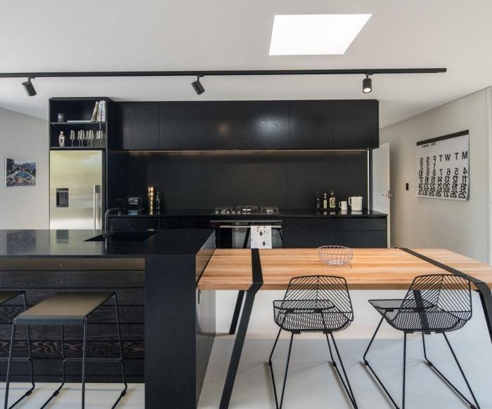 cuisine peinture noir mat équipée d'un ilot central avec table intégrée, en bois naturel contrastant avec la structure de base