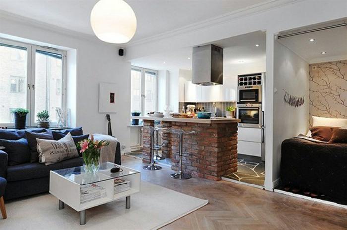 salon à déco scandinave, table basse scandinave avec rangement et plateau en verre, tapis blanc, sol en parquet, sofas gris, bar en briques
