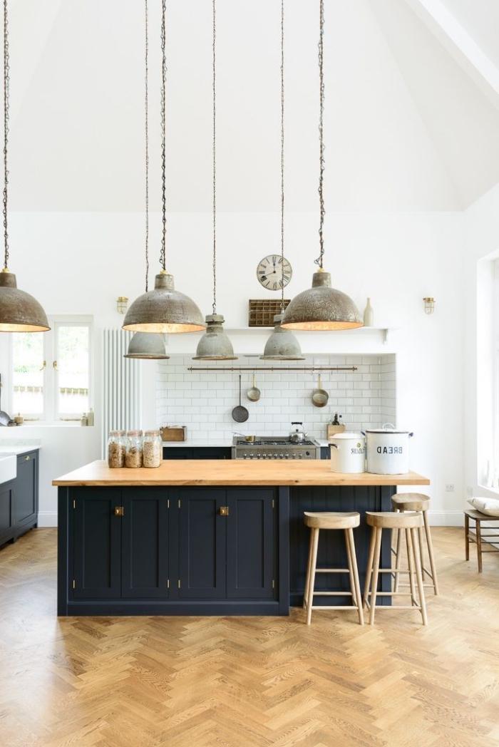 une grande cuisine aménagée en style atelier avec un ilot central cuisine deux couleurs surmonté des luminaires suspendus industrielles