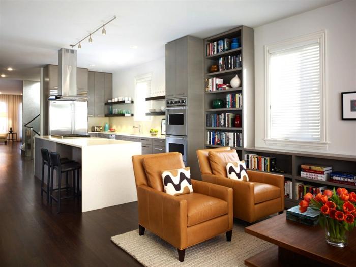 aménagement cuisine ouverte, fauteuils en cuir, table en bois, tapis beige, ilot de cuisine blanc, étagère bibliothèque