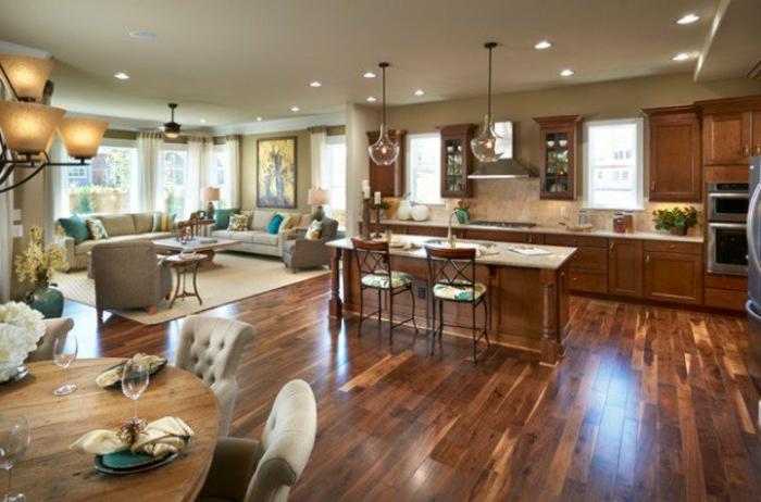 grand salon et cuisine, ilot de cuisine, sol en bois, salon gris, placards en bois, lampes en verre