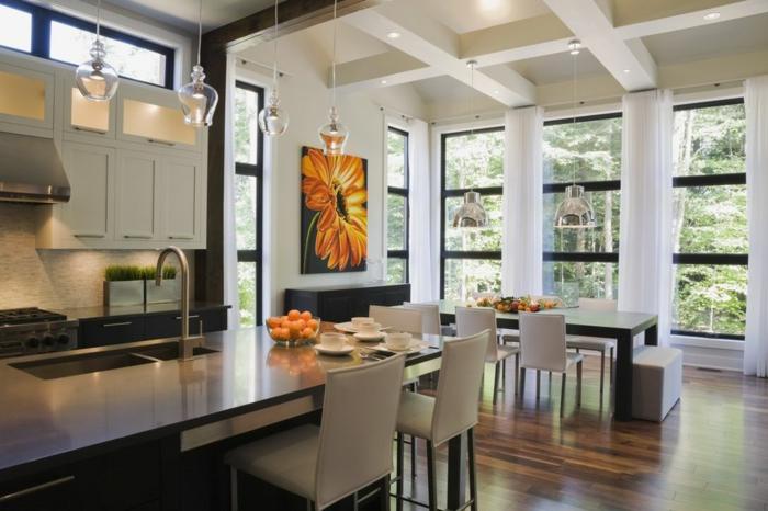 petite cuisine ouverte sur salon, ilot de cuisine avec évier, chaises blanches, plafond suspendu
