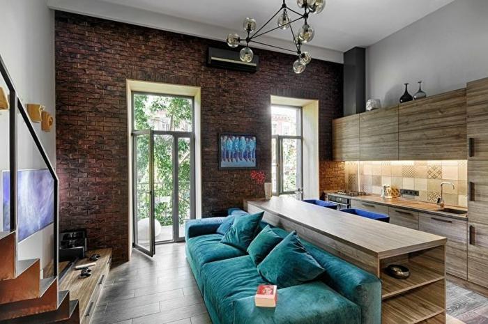 aménagement cuisine petite surface, lampe molécules, escalier loft et sofa bleu moelleux, comptoir en bois clair
