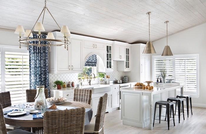 meuble cuisine tout en blanc avec ilot central blanc et tabourets de bar metalliques noires, parquet clair, table bois entourée de chaises en rotin