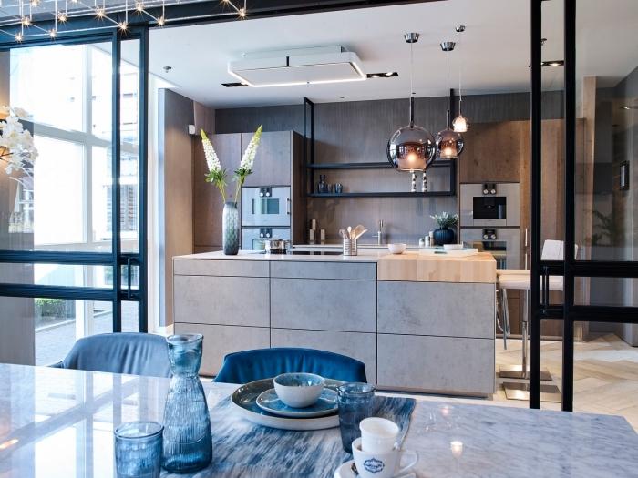 cuisine semi-ouverte séparée du séjour avec une verrière d'atelier, équipée d'un ilot de cuisine en béton à planche en bois intégrée