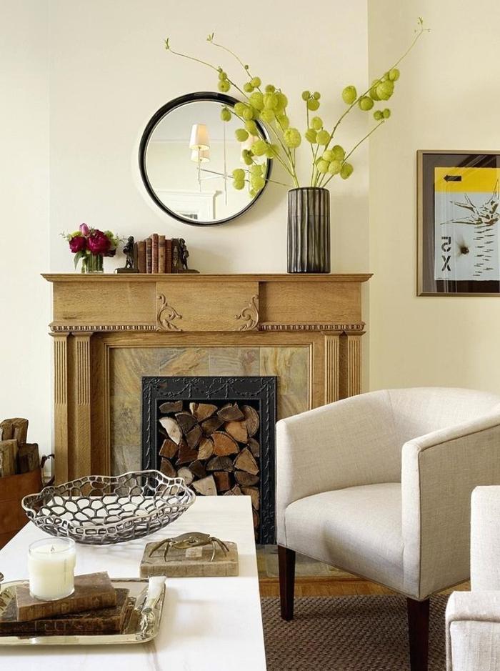 miroir rond décoratif, cheminée murale en bois, fauteuils blancs, vase avec plante verte