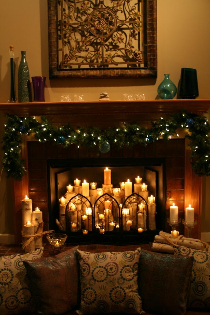 fausse cheminée décorative, plusieurs bougies allumées, lampes lumineuses et coussins déco