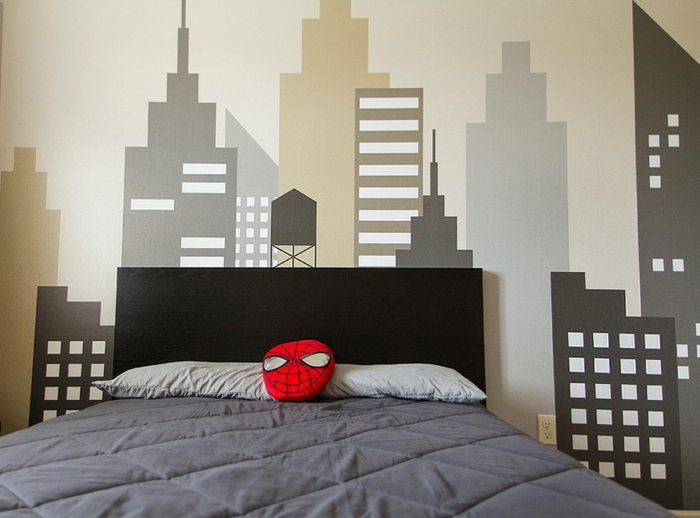 coussin en forme de masque de spiderman, dessins muraux gratte-ciel, grand lit dans une chambre gris et blanc