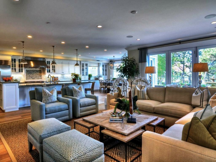 table basse en bois et fer, fauteuils et tabourets gris, sofas beiges, grand comptoir de cuisine, separation cuisine salon